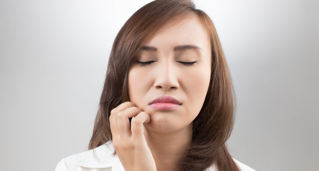 woman holding numb mouth